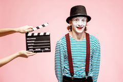 Portrait of a pantomime with cinematography clapperboard. Portrait of an actor as a pantomime with cinematography clapperboard on the pink background stock photography
