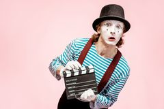 Portrait of a pantomime with cinematography clapperboard. Portrait of an actor as a pantomime with cinematography clapperboard on the pink background stock image