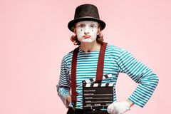 Portrait of a pantomime with cinematography clapperboard. Portrait of an actor as a pantomime with cinematography clapperboard on the pink background stock images