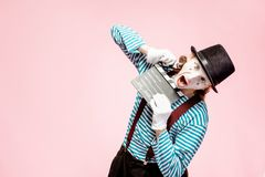Portrait of a pantomime with cinematography clapperboard. Portrait of an actor as a pantomime with cinematography clapperboard on the pink background royalty free stock images