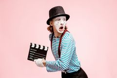 Portrait of a pantomime with cinematography clapperboard. Portrait of an actor as a pantomime with cinematography clapperboard on the pink background royalty free stock image