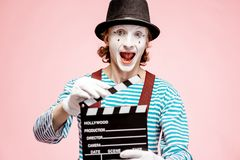 Portrait of a pantomime with cinematography clapperboard. Portrait of an actor as a pantomime with cinematography clapperboard on the pink background royalty free stock photos