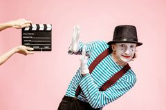 Portrait of a pantomime with cinematography clapperboard. Portrait of an actor as a pantomime with cinematography clapperboard on the pink background stock photo