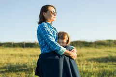 Portrait of parent and child. Mother hugs her little daughter. Nature background, rural landscape, green meadow Royalty Free Stock Photos