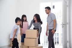 Parent and kids with cardboard box. moving to new house. Portrait of parent and kids with cardboard box. moving to new house concept Stock Photos