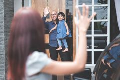 Kid waving goodbye to parent. Portrait of parent saying goodbye to their daughter for work stock image