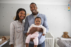 Portrait Of Parents With Baby Daughter In Nursery Royalty Free Stock Image