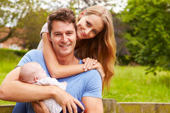 Portrait Of Parents With Baby On Walk In Countryside Stock Photo