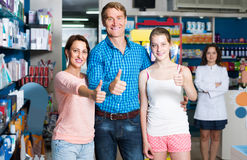 Portrait of parents with daughter teenager looking satisfied in. Portrait of glad european  parents with daughter teenager looking satisfied in drug store and Royalty Free Stock Photography