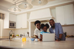 Portrait of parents and daughter using laptop in kitchen Royalty Free Stock Images