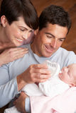 Portrait Of Parents Feeding Newborn Baby At Home Royalty Free Stock Photo