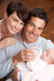 Portrait Of Parents Feeding Newborn Baby At Home Royalty Free Stock Photography