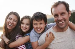 Portrait Of Parents Giving Children Piggyback Ride In Countryside royalty free stock photos