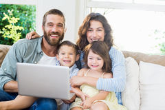 Portrait of parents and kids using laptop in living room. At home Royalty Free Stock Photography