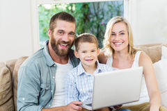 Portrait of parents and son using laptop in living room. At home Royalty Free Stock Photo