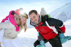 Portrait of parents with their children on their back in snowy mountains Royalty Free Stock Photos