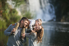 Portrait of a parents with their son. Son kisses mother. Portrait of a young parents with their son near a waterfall. The son sits on his father shoulders and Royalty Free Stock Image
