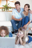 Portrait of parents watching their children using a laptop. In their living room Royalty Free Stock Images