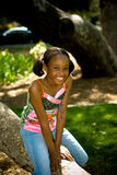 Portrait In The Park. A young african american girl smiling - posed by a tree Stock Image