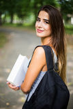 Portrait in park of a beautiful tanned teen student girl. Student girl outside in summer park smiling happy Stock Image