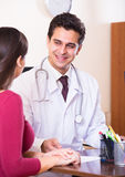 Portrait of patient and therapeutist at desk in modern clinic Royalty Free Stock Photo