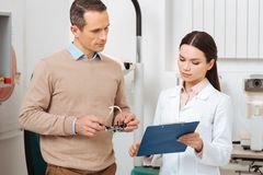 Portrait of patient with trial frame in hands at the oculists reception. In clinic stock photo