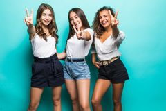 Portrait of peaceful three multiethnic cheerful girls in summer look gesturing v-signs with two hands isolated on green background stock photography