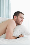 Portrait of a peaceful young man lying on his belly Stock Photography