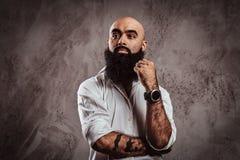 Portrait of a pensive bearded Arabian male wearing a white shirt, looking away. stock photo