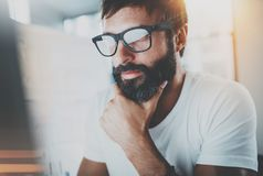 Portrait of pensive bearded designer working at the modern office loft.Horizontal. Blurred background.Flares effect. royalty free stock photography