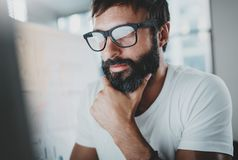 Portrait of pensive bearded designer working at the modern office loft.Horizontal. Blurred background. stock image