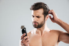 Portrait of a pensive bearded guy looking at electric shaver. Isolated over white background Stock Image