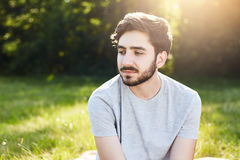 Portrait of pensive bearded male with stylish hairdo looking down with his charming big dark eyes thinking over his life enjoying. Stillness and being alone Stock Photo