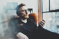 Portrait of pensive bearded man wearing glasses,headphones and listening to music at modern home.Guy sitting in vintage Royalty Free Stock Image