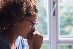 Portrait of pensive black woman standing beside window. Lonely black woman near window thinking about something stock photography