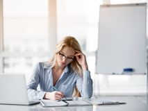 Thoughtful young woman making notes at workplace. Portrait of pensive blond businesswoman writing thoughts in notebook. She is sitting at table in office Royalty Free Stock Photography