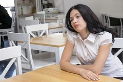 Dreamy young woman posing inside. Portrait of pensive brunette model sitting in cafe with nice interior and looking away. Brooding girl waiting for order. Copy royalty free stock image