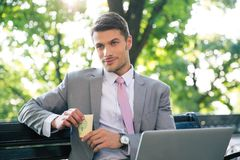 Portrait of a pensive businessman sitting on the bench. With laptop and cup with coffee Royalty Free Stock Image