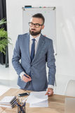 Portrait of pensive businessman standing at workplace with papers Royalty Free Stock Photos