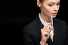 Portrait of pensive businesswoman with pen in hand Royalty Free Stock Image