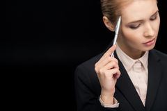 Portrait of pensive businesswoman with pen in hand Stock Photo