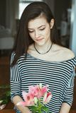 Pensive Caucasian young beautiful woman model with messy long hair in striped t-shirt at home with flowers Stock Image