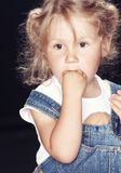 Portrait of a pensive cute little girl in denim overalls, sitting in a studio on black background. Royalty Free Stock Photography