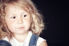 Portrait of a pensive cute little girl in denim overalls, sitting in a studio on black background. Stock Photo