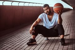 Portrait of a pensive dark-skinned guy dressed in a white shirt and sports shorts holds a basketball while sitting on a. Pensive dark-skinned guy dressed in a Stock Photos