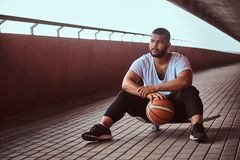 Portrait of a pensive dark-skinned guy dressed in a white shirt and sports shorts holds a basketball while sitting on a. Skateboard on a footway under a bridge Royalty Free Stock Photo