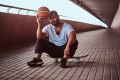 Portrait of a pensive dark-skinned guy dressed in a white shirt and sports shorts holds a basketball while sitting on a. Skateboard on a footway under a bridge Stock Photo