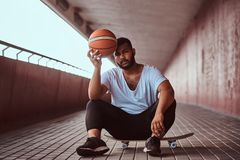 Portrait of a pensive dark-skinned guy dressed in a white shirt and sports shorts holds a basketball while sitting on a. Skateboard on a footway under a bridge Stock Images