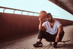 Portrait of a pensive dark-skinned guy dressed in a white shirt and sports shorts holds a basketball while sitting on a. Skateboard on a footway under a bridge Stock Image