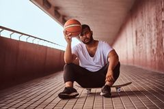 Portrait of a pensive dark-skinned guy dressed in a white shirt and sports shorts holds a basketball while sitting on a. Skateboard on a footway under a bridge Royalty Free Stock Photography